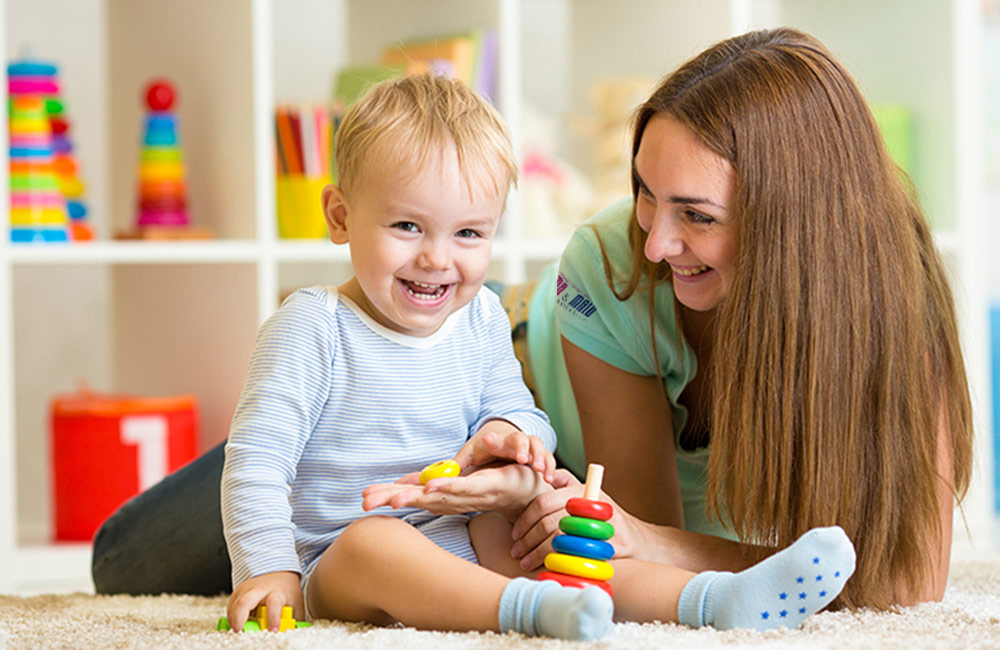 happy mother and child son play together indoor at home